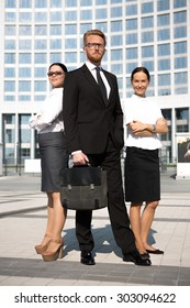 Photo of businesspeople in full length isolated on office building. Man in glasses posing with brief case, businesswomen with arms crossed.