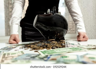 Photo of businesswoman standing behind piggy bank on pile of money