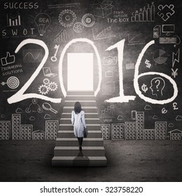 Photo of businesswoman walking on the stairs toward a door with numbers 2016 and scribble