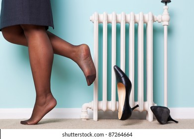 Photo of a businesswomans legs with stockings on kicking her high heel shoes off as she returns home after a hard day at work. Motion blur on one of the shoes.