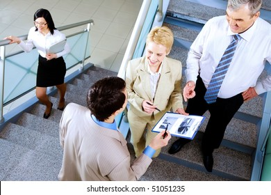Photo of busy partners discussing papers while on stairs of office building