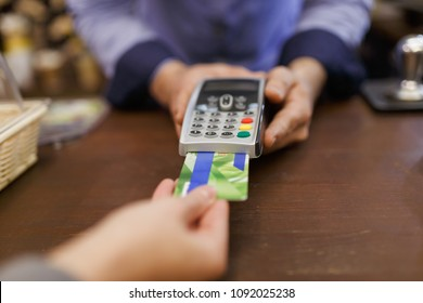 Photo of buyer with bank card and seller with terminal in hand