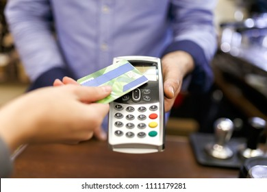 Photo of buyer man with bank card and seller with terminal in hand
