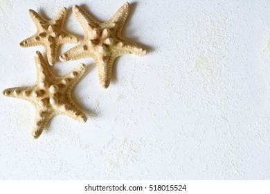 Photo by three starfishes in the corner of white background with sand.