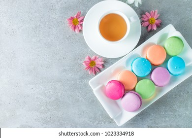 Photo of cake macarons, gift box, tea, coffee, cappuccino and flowers. Sweet romantic food macaroon concept. Morning breakfast and presents. Valentine's day concept.