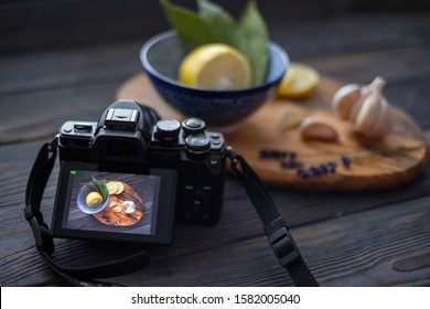 Photo camera of with food style shot on the screen near the set