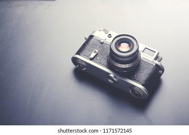 photo camera on black table background