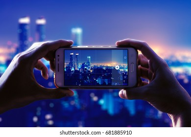 Photo camera of a smartphone. View through the screen at the time a young woman takes a photo of a city at night. Cityscape.