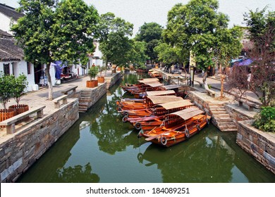 Photo of a canal in ancient Tongli watertown near Suzhou, China with traditional boats and old houses on both sides, filtered and stylized to resemble an oil painting