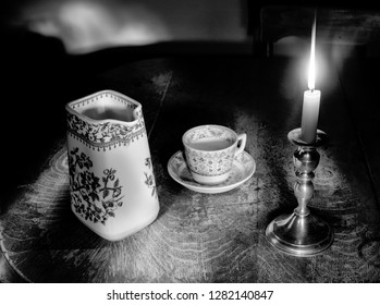 Photo of a candle and candleholder, antique teapot and teacup.