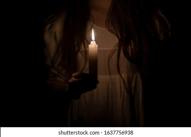 Photo of a candle at night holding by a young girl in an old white dress.  Focus on the candle. Dark background. Scary horror concept.