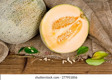 Photo of cantaloupe melon with slice and leaves on burlap and wooden board