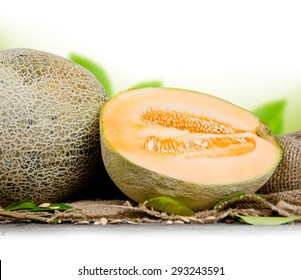 Photo of cantaloupe melon with slice and leaves on burlap with white space