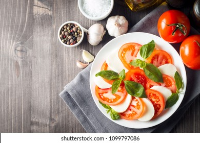 Photo of Caprese Salad with tomatoes, basil, mozzarella, olives and olive oil on wooden background. Italian traditional caprese salad ingredients. Mediterranean, organic and natural food concept.