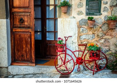 Photo capturing the vibrant cobbled streets of Spain. Photo shot in Valldemossa, village in Mallorca or Majorca Spain, a Balearic island. It depicts a stationary red bike adorned with flowers