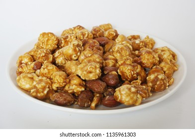 A photo of caramel popcorn on white plate isolated on white background, close up