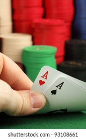 Photo of a card player holding two aces in focus, and a stack of gambling chips blurry in the background.