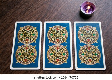 Photo cards for fortune telling or playing. Tarot cards on a wooden background. With a burning candle.