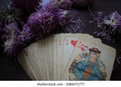 Photo cards for fortune telling or playing. Old cards on a wooden background with flowers.