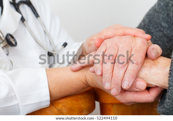 Photo of a caregiver hand touching elderly patients hand