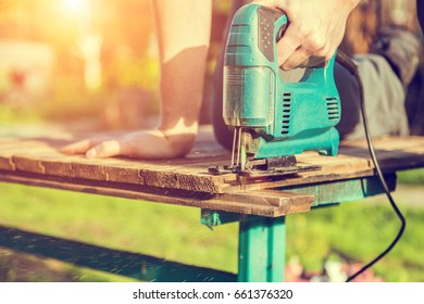 Photo of carpenter working with electric jigsaw in summer on street