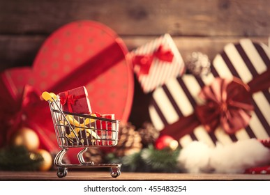 photo of the cart for shopping with gifts on the christmas decorations background