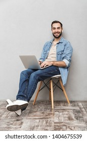 Photo of casual attractive man having beard typing laptop and using earpods while sitting on chair isolated over gray wall