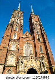 Photo of Cathedral Church in Wroclow. Romam Catholic gothic architecture church. Two towers on blue sky background on sunny day in summer. Facade view. Wroclaw, Poland.
