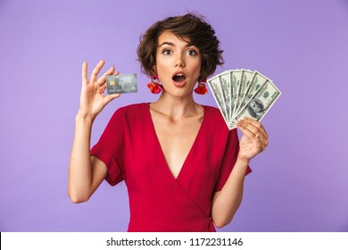 Photo of caucasian brunette woman 20s wearing big straw hat smiling while holding credit card and fan of dollar cash isolated over white background