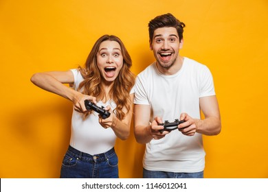 Photo of caucasian couple man and woman playing together video games using joysticks isolated over yellow background