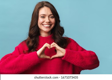Photo of caucasian happy woman with long brown hair smiling and showing heart shape with hands isolated over blue background