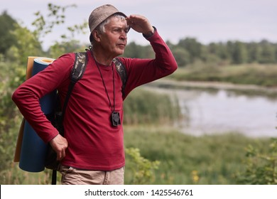 Photo of caucasian man hipster man with backpack and rug in nature background. Relax time on holiday, eldery male looking far away, dressed casual red shirt and cap. Traveling and active rest concept.