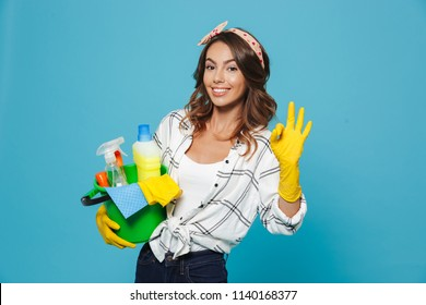 Photo of caucasian pretty housemaid 20s wearing yellow rubber gloves for hands protection holding bucket with cleaning supplies isolated over blue background