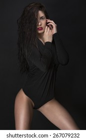 Photo of a caucasian woman posing with a black bodysuit, wet hair, perfect nails in front of a black background