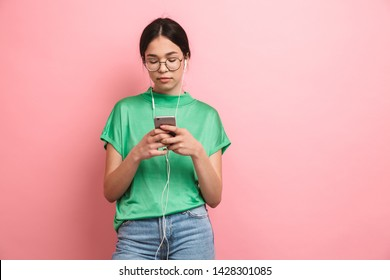 Photo of Photo of caucasian young girl wearing round eyeglasses using earphones while holding smartphone isolated over pink background