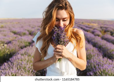 Photo of caucasian young woman in dress holding bouquet of flowers while walking outdoor through lavender field in summer