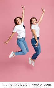 Photo of cexcited two young twin sisters with beautiful smile jump up over pink background.