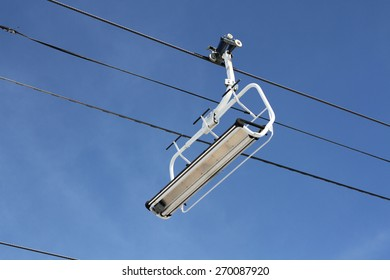 Photo of a chair lift on a mountainous ski resort as used by skiers and snowboarders in winter.