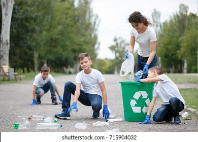 Photo of charity environment concept. Sunny day. Children in blue jeans and white t-shirt with colorful: blue and green recycle bin with label. Cleaning in park toghether. Team work.