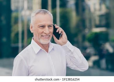 Photo of charming cute mature worker man wear formal shirt talking modern device outdoors city street