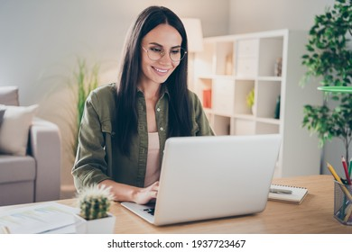Photo of charming positive person sit behind desktop look use laptop have good mood working home indoors