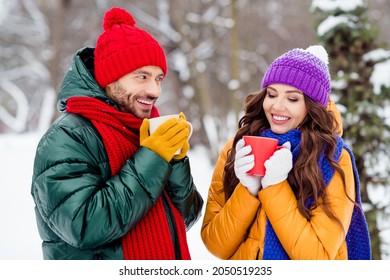 Photo of charming pretty marriage couple wear windbreakers smiling drinking coffee walking snowy weather outside park