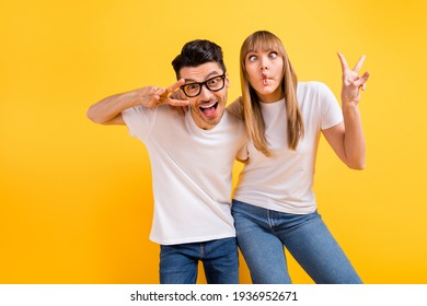 Photo of charming pretty young couple wear white t-shirt spectacles dancing showing v-signs isolated yellow color background