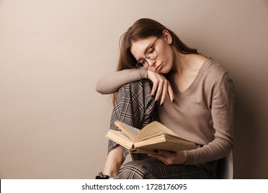 Photo of charming sad woman in eyeglasses reading book and sitting on chair isolated over grey wall