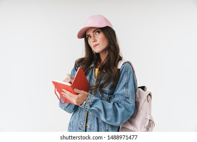 Photo of charming student girl wearing cap thinking while writing down notes at diary book isolated over white background