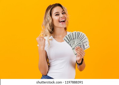 Photo of charming woman in basic clothing holding fan of dollar money isolated over yellow background