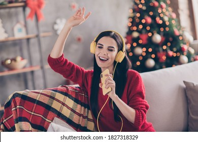 Photo of charming young lady hold sing telephone open mouth raise hand wear headphones red sweater in decorated living room indoors