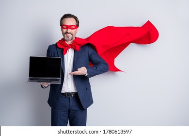 Photo of cheerful aged mature business guy superhero costume hold laptop showing new device sale manager modern user wear suit red face mask cloak flying isolated grey background