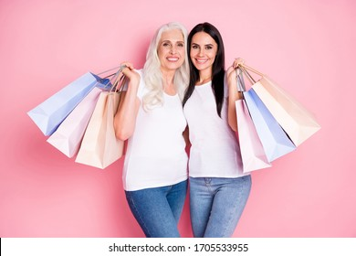 Photo of cheerful aged mother young daughter ladies holding many shopping packs attend store together wear white t-shirts jeans isolated pastel pink color background