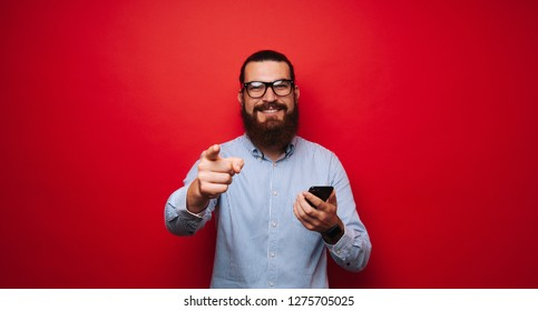 Photo of cheerful bearded man holding a phone, looking and pointing to camera